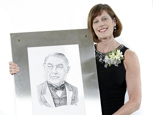 CMA President Cindy Forbes, MD holding framed portrait of Sir Charles Tupper.